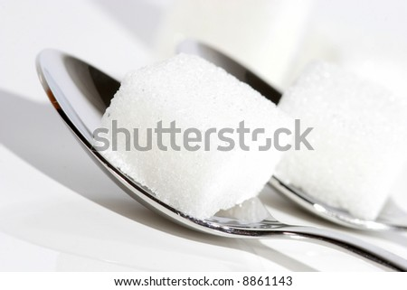 sugar cubes on spoons - stock photo