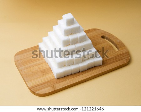 Sugar cubes pyramid on a yellow background - stock photo
