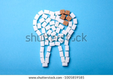 Sugar destroys the tooth enamel and leads to tooth decay. Sugar cubes are laid out in the form of a tooth and brown sugar symbolizes caries.