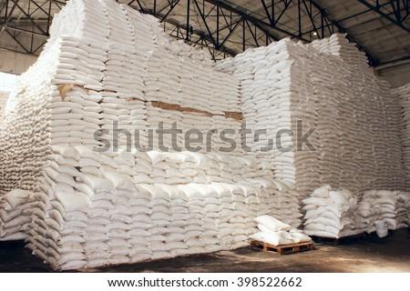 Sugar in a Warehouse. Bags of sugar. Large food warehouse with sugar sacks. Sugar beet factory - stock photo