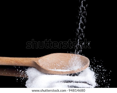 sugar in a wooden spoon on black