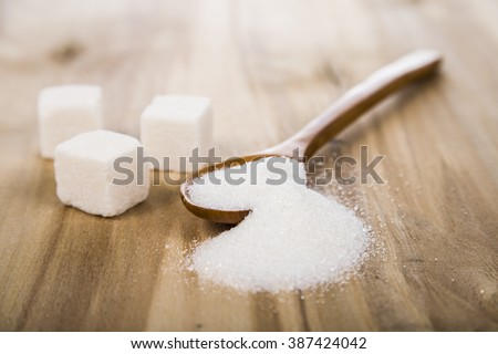 Sugar in a wooden spoon on the table