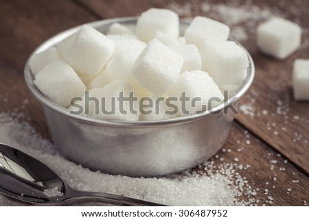 Sugar in bowl on wooden table - stock photo