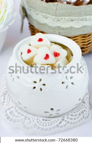 Sugar in shape of heart in white sugar bowl - stock photo