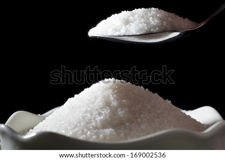 Sugar is filled in a sugar bowl from a teaspoon - stock photo