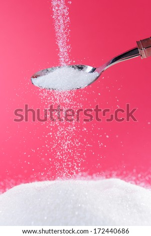 Sugar on red background - stock photo