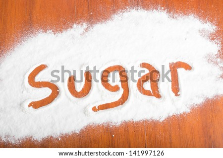 Sugar sign with flour Artwork With Food And Handprints, Fun background with human handpints in scattered flour on a wooden tabletop.