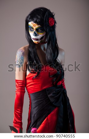 Sugar skull girl in red evening dress, studio shot