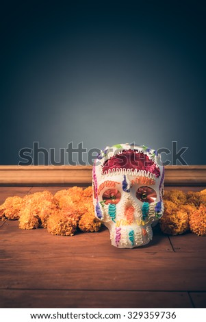 "sugar skull used for ""dia de los muertos"" celebration in a grey background with cempasuchil flowers - stock photo"