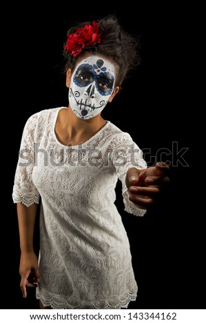 Sugar skull with a sorrowful face reaching out to the viewer. - stock photo