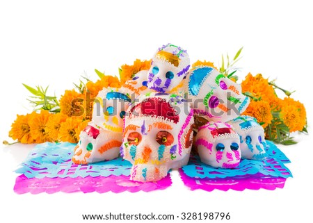 "sugar skulls used for ""dia de los muertos"" celebration isolated on white with cempasuchil flowers - stock photo"