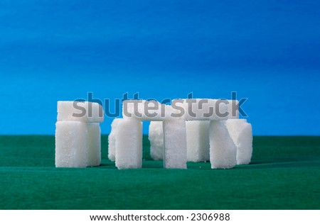 Sugar stonehenge on green & blue background - stock photo