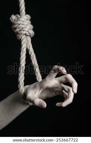 Suicide and depression topic: human hand hanging on rope loop on a black background - stock photo