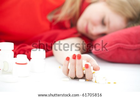suicide test -  young depressive woman lying on red pillow, focus selected on hand with drugs - stock photo