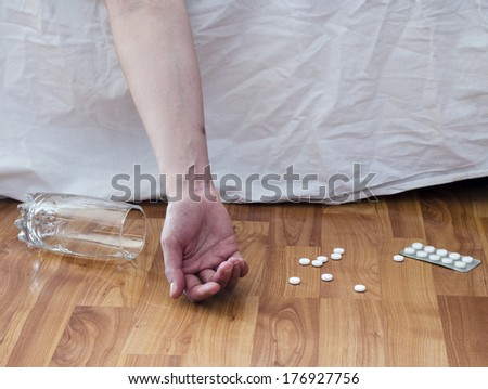 Suicide with pills. Drug abuse concept, passive hand on floor with spilled pills and glass of water