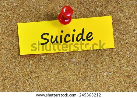 Suicide word on notepaper with brown cork background - stock photo