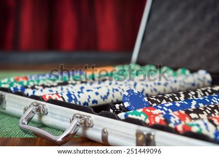 Suit case full of Poker chips / Casino table - stock photo