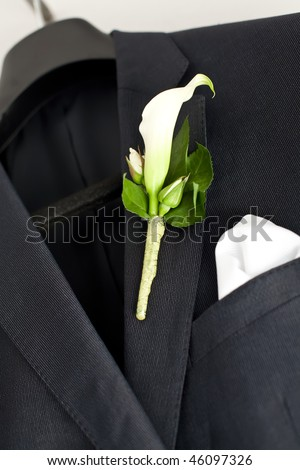 Suit jacket hanging on a hanger with a boutonniere in place. - stock photo