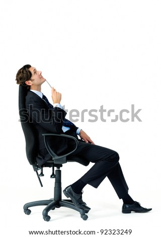 Suit wearing businessman ponders and looks overhead while holding a pen - stock photo