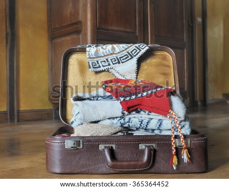 suitcase full of sweaters on tue wooden floor in a room  - stock photo