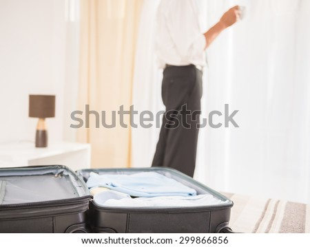 Suitcase on the bed in hotel room. Close-up of man looking at the window.