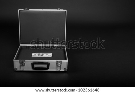 suitcase with a bunch of money on a black background