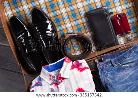 Suitcase with clothes of elegant man. Suitcase with fashionable clothes and accessories. - stock photo