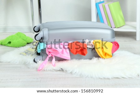 Suitcase with clothes on mat on room background - stock photo
