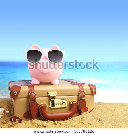 Suitcase with piggy bank in sunglasses on tropical beach - stock photo
