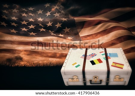 Suitcase with stickers against digitally generated american flag rippling over grass - stock photo