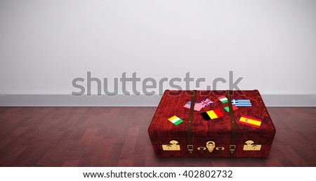Suitcase with stickers against room with wooden floor - stock photo