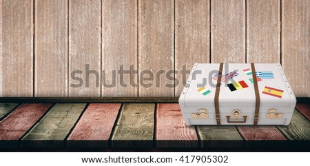 Suitcase with stickers against wooden board - stock photo
