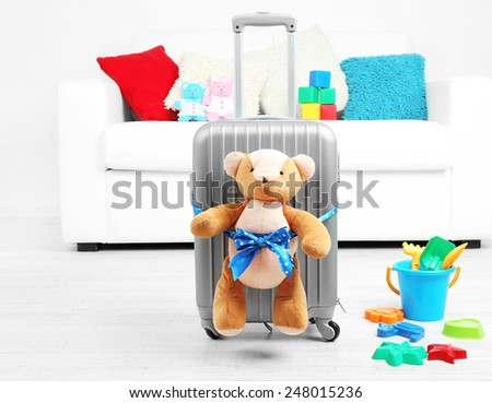 Suitcase with teddy bear and child toys in room on white sofa background - stock photo