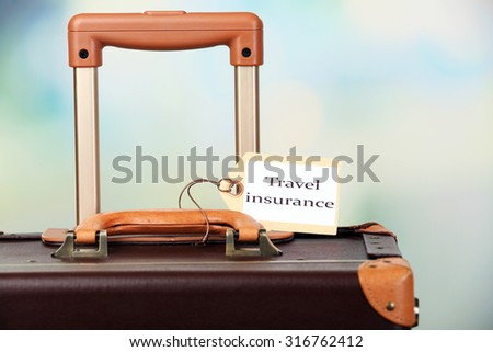Suitcase with TRAVEL INSURANCE label on light blurred background - stock photo