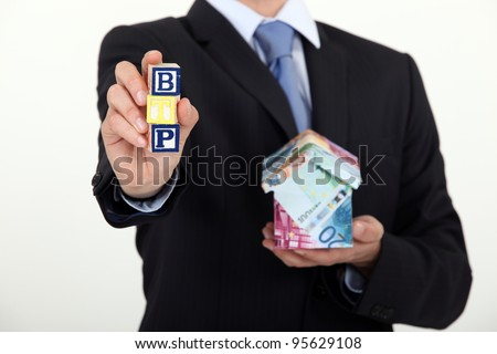 Suited man with a house made of banknotes - stock photo