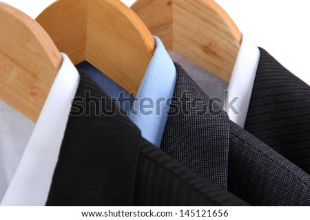 Suits with shirts on hangers on light background - stock photo
