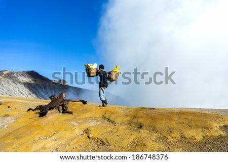 sulfur worker at kawah ijen - stock photo