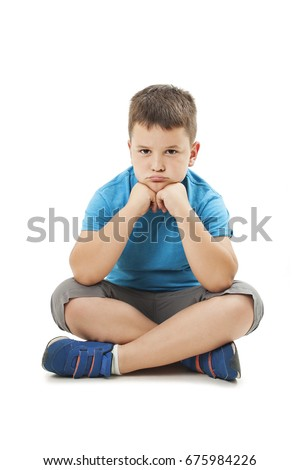 Sulky angry young boy child, sulking and pouting. Isolated on white background