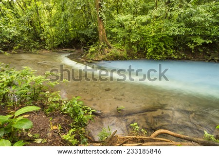 Sulphur from one stream reacts with sediment from another to form the Cerulean blue waters of the Rio Celeste in Volcan Tenorio National Park, Costa Rica. - stock photo