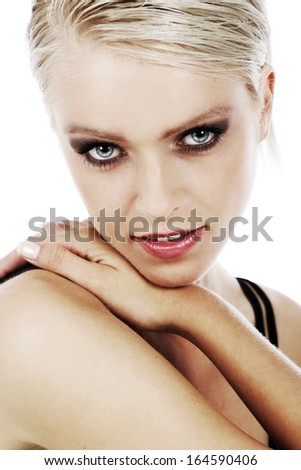Sultry green-eyed beautiful blond woman with dark eye makeup resting her chin on her shoulder looking at the camera with a seductive look, isolated on white - stock photo