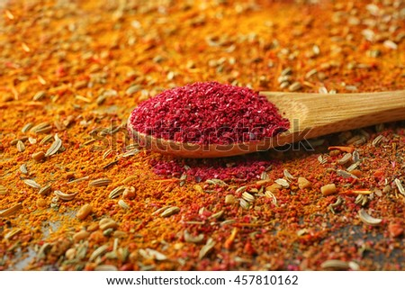 Sumac in wooden spoon on mixed spices background - stock photo