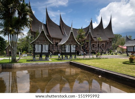 SUMATERA - AUGUST 23: Tourists and photographers visit the Gadang House in Padang Panjang, West Sumatra, Indonesia on August 23, 2013.  The 'Minangkabau' architecture features horns on rooftops.  - stock photo