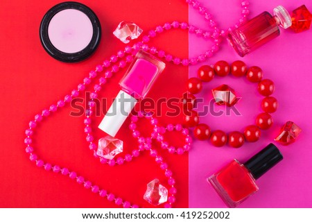 Summer Accessories and Cosmetics for relaxing on fuchsia background - sunglasses, lipstick, powder, colored beads, nail polish. View from above. Flat lay. - stock photo