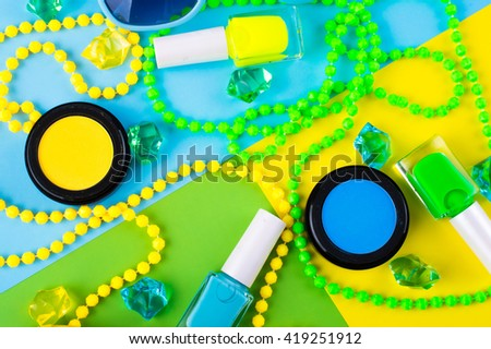 Summer Accessories and Cosmetics for rest on a colorful background - sunglasses, lipstick, powder, colored beads, nail polish. View from above. Flat lay. - stock photo