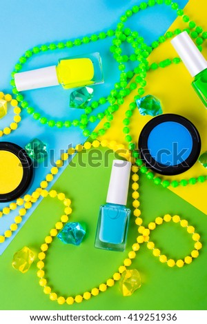 Summer Accessories and Cosmetics for rest on a colorful background - sunglasses, powder, colored beads, nail polish. View from above. Flat lay. - stock photo