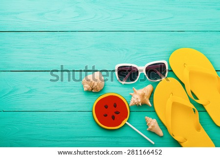 Summer accessories and shells with candy on blue wooden background. - stock photo