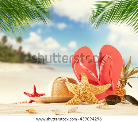 Summer accessories on sandy beach, blur sea on background. Summer exotic relaxation concept. Copyspace for text