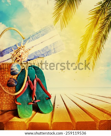 Summer accessories, swimsuit, sun glasses, bag and flip-flops. Closeup of summer beach bag  - stock photo