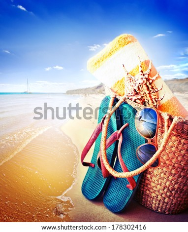 Summer accessories, swimsuit, sun glasses, bag and flip-flops. Closeup of summer beach bag and straw hat on sandy beach. - stock photo