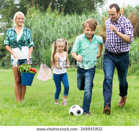 Summer activity - cheerful young married couple with children playing ball in the country home. Focus on the young girl